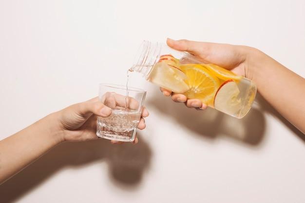 Männliche hand gießt entgiftungswasser in glas. detox-wasser, fitness, gesundes ernährungskonzept. frisches zitronengurken-minze-detox-getränk im glas auf weißem holztisch