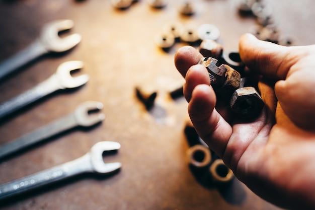 Männliche hand hält alte nussschlüsselschlüssel auf rostigem metallschreibtisch defokussiert