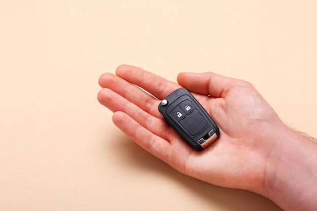 Männliche hand hält autoschlüssel auf beigem hintergrund. konzeptauto, mietwagen, geschenk, fahrunterricht, führerschein. flache lage, draufsicht