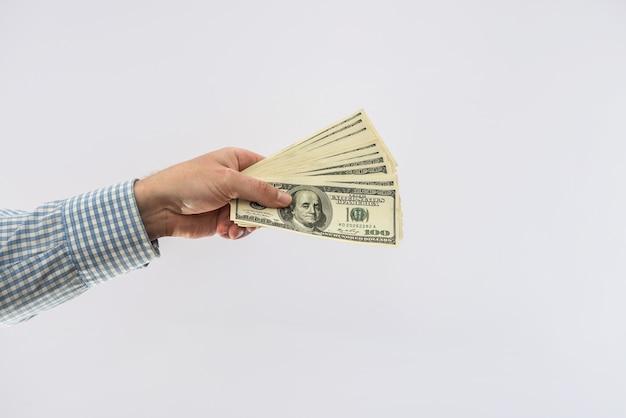 Männliche hand hält banknote von 100-dollar-scheinen isoliert. finanzkonzept
