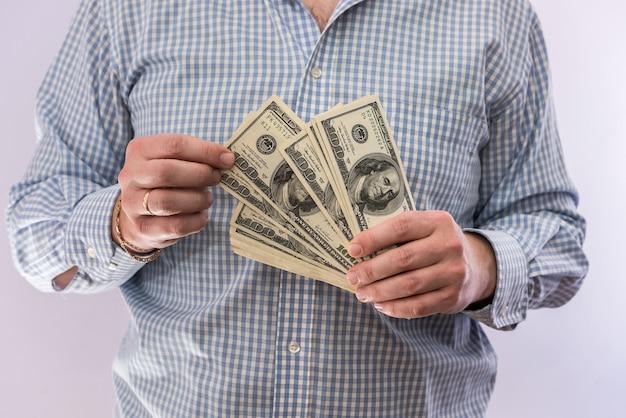 Männliche hand hält banknoten von 100-dollar-scheinen isoliert. finanzierungskonzept