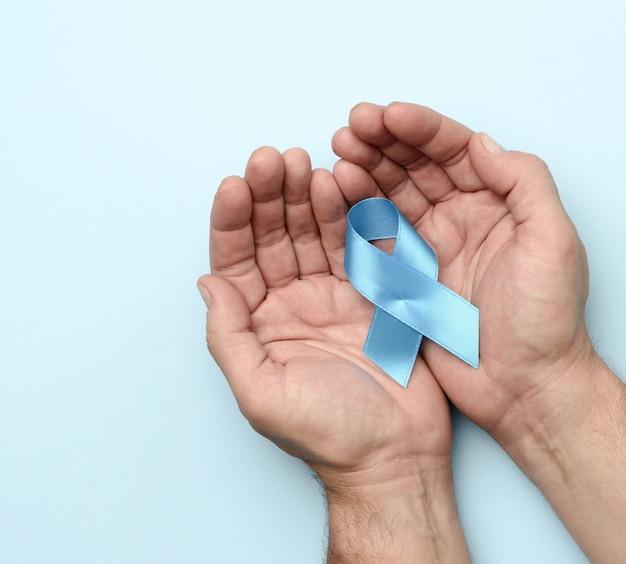 Männliche hand hält blaues seidenband symbol des kampfes und der behandlung von prostatakrebs