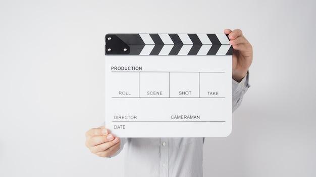 Männliche hand hält clapper board oder filmschiefer in der videoproduktion, film-, kinoindustrie auf weißem hintergrund.