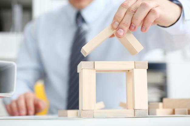 Männliche hand hält das dach zum verschluss in der hand gegen den hintergrund der immobiliendienstleistungen des spielzeughausverkaufskauf-mietkonzeptes auf dem markt.