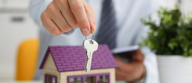 Männliche hand hält den schlüssel zum schloss in der hand