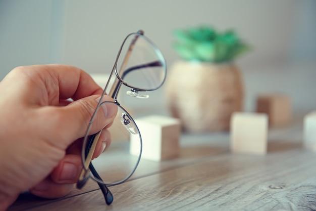 Männliche hand hält dünn umrandete brille und ruht auf einem holztisch