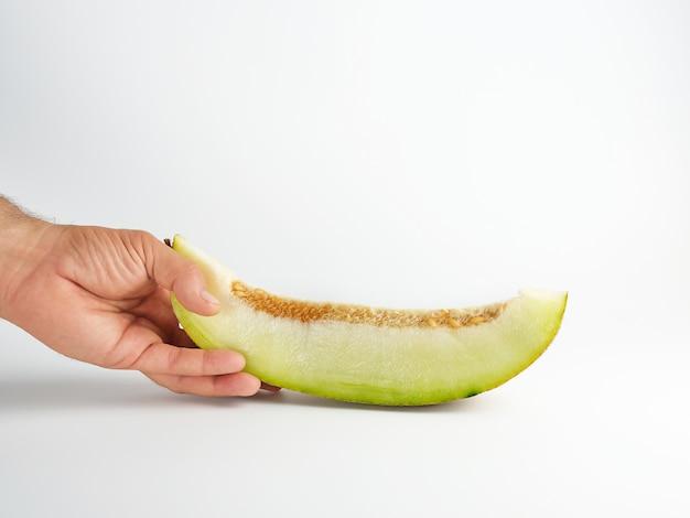 Männliche hand hält ein stück reife melone mit samen