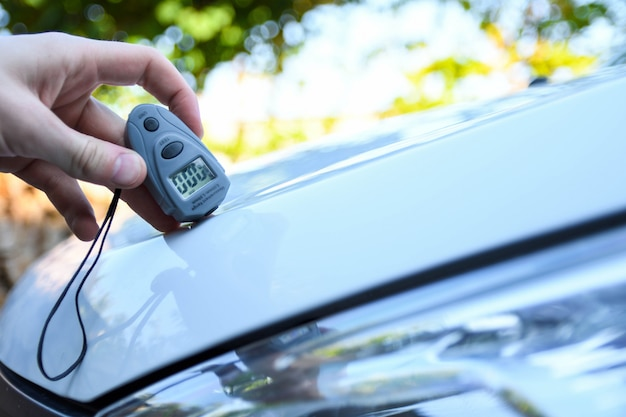 Männliche hand hält gerät zur messung der schichtdicke vor dem polieren auto. lackierung mit lehre. polnisches autokonzept