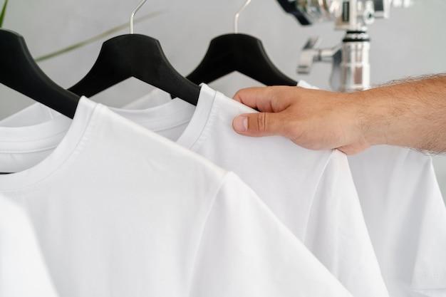 Männliche hand hält kleiderbügel mit leerem weißem t-shirt, nahaufnahme