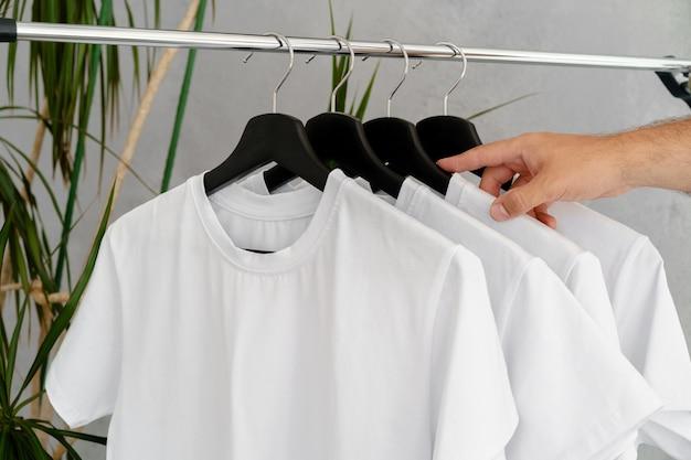 Männliche hand hält kleiderbügel mit leerem weißem t-shirt