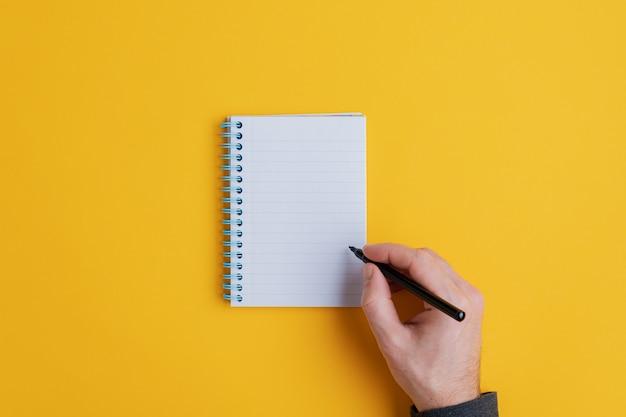 Männliche hand hält schwarzen stift bereit zu schreiben