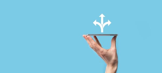 Männliche hand hält symbol mit drei richtungen symbol auf blauem hintergrundn zweifel müssen zwischen wählen...