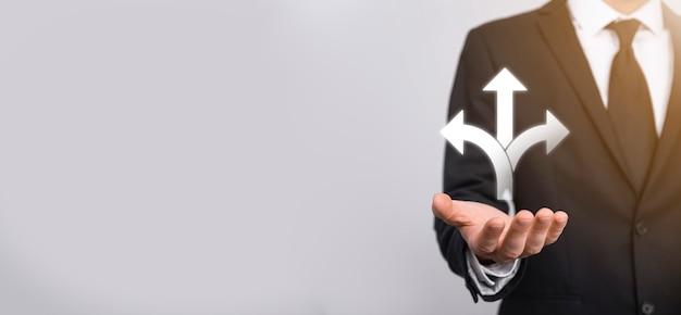 Männliche hand hält symbol mit drei richtungen symbol auf dunklem hintergrund. zweifel, zwischen drei verschiedenen möglichkeiten wählen zu müssen, die durch pfeile angezeigt werden, die in die entgegengesetzte richtung weisen. wege