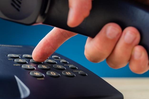 Männliche hand hält telefonempfänger, der telefonnummer wählt
