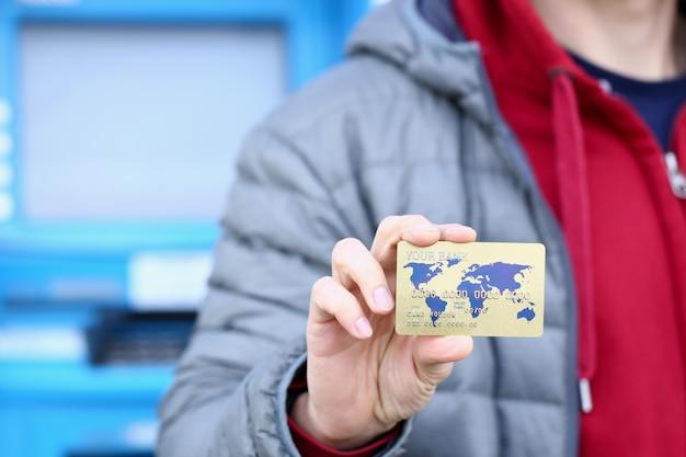 Männliche hand halten bank plastikkarte gegen geldautomaten