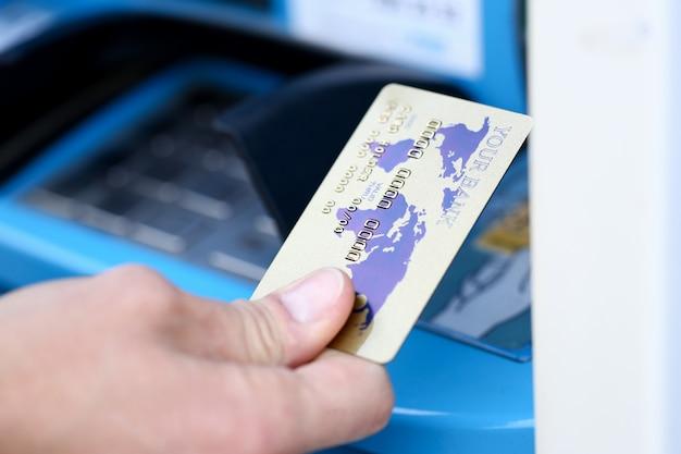 Männliche hand halten bankplastikkarte aganist atm