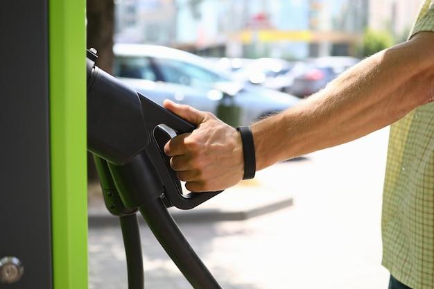 Männliche hand halten pistole einen elektrischen ladungsstadtstationshintergrund