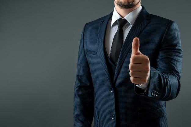 Männliche hand im anzug zeigt daumen hoch geste auf grauem hintergrund. konzept ok, genehmigung, nahaufnahme.