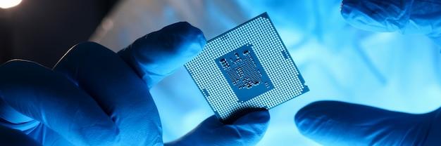 Männliche hand in blauen schutzhandschuhen halten mikroprozessor-nahaufnahme