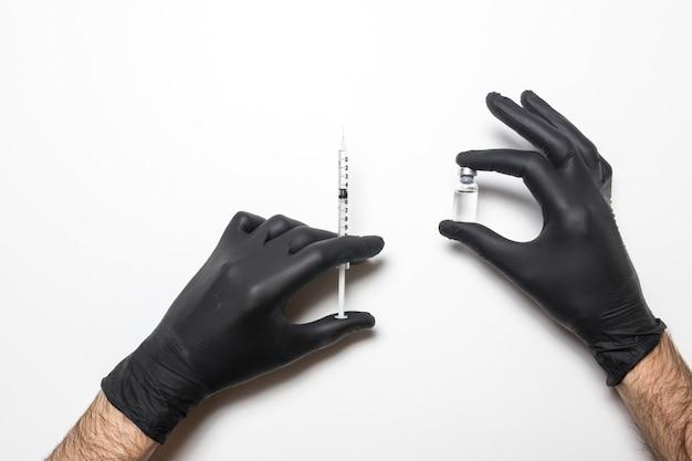 Männliche hand in einem medizinischen handschuh mit einem impfstoff auf einer weißen oberfläche