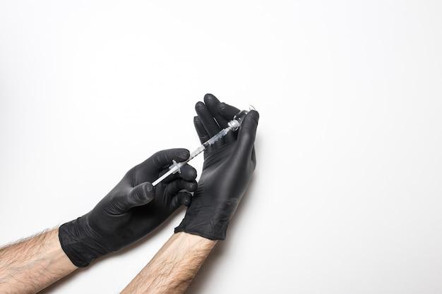 Männliche hand in einem medizinischen handschuh mit einem impfstoff auf einer weißen wand