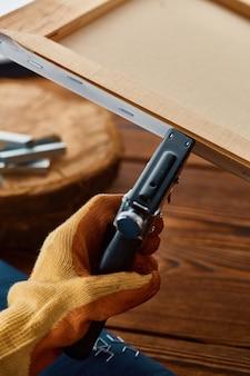 Männliche hand in hand hält hefter, nahaufnahme. professionelles instrument, tischlerausrüstung, holzbearbeitungswerkzeuge