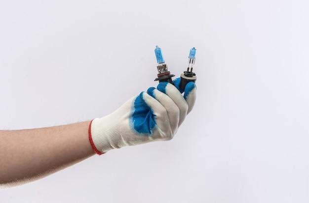 Männliche hand in handschuhen, die eine autolampe für scheinwerfer isoliert, autoausrüstung halten