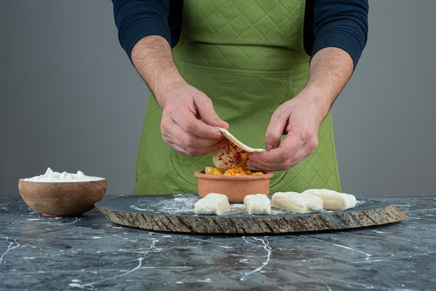Männliche hand in handschuhen, die essen auf marmortisch machen.