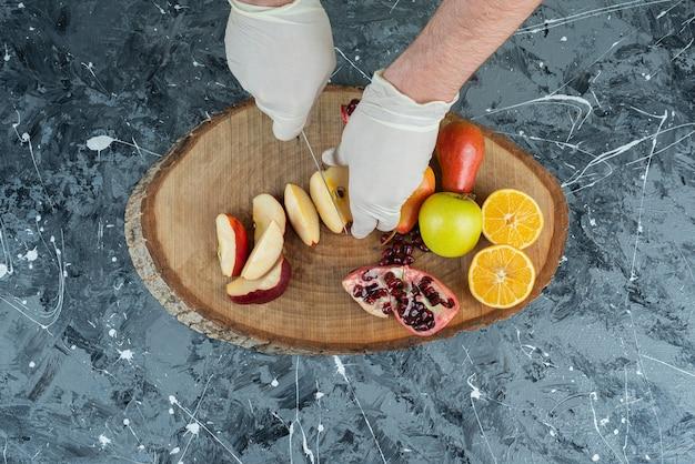 Männliche hand in handschuhen, die frischen apfel auf marmortisch schneiden.