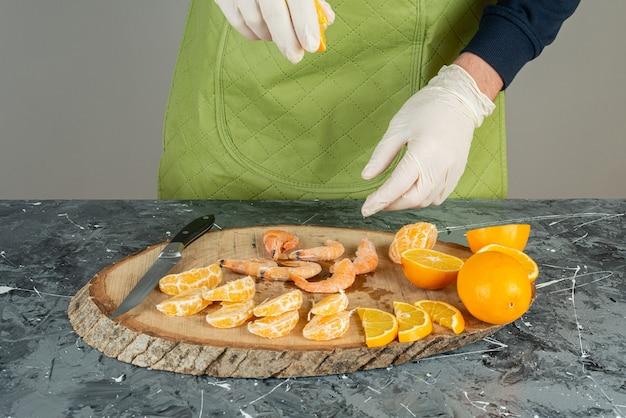 Männliche hand in handschuhen, die garnelen auf marmortisch salz hinzufügen.