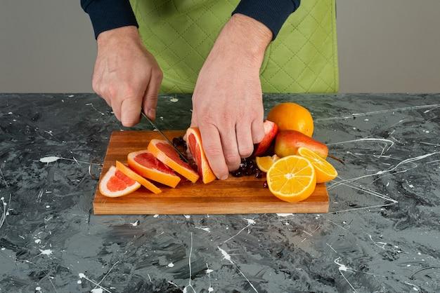 Männliche hand in handschuhen, die saftige grapefruit auf marmortisch schneiden.