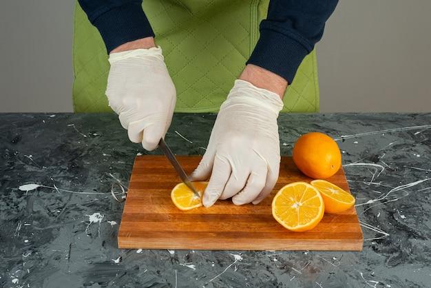 Männliche hand in handschuhen, die saftige orange auf marmortisch schneiden.