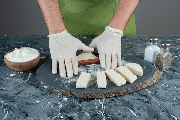 Männliche hand in handschuhen, die teig auf marmortisch machen.