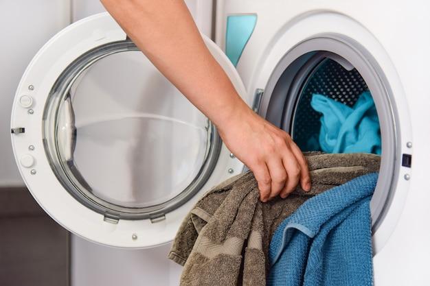 Männliche hand legt frottierhandtücher in die trommel der waschmaschine.