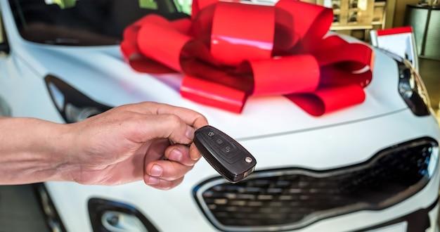 Männliche hand mit autoschlüsseln mit auto auf hintergrund. mieten oder kaufen