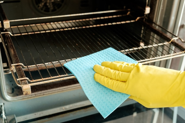 Männliche hand mit den handschuhen, die ofen säubern