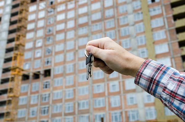 Männliche hand mit den schlüsseln zur wohnung auf der oberfläche eines mehrstöckigen unfertigen hauses. konzept, die schlüssel zur wohnung zu bekommen.
