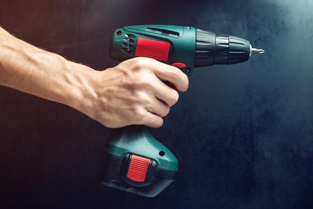 Männliche hand mit einem schraubendreher zum schrauben von schrauben