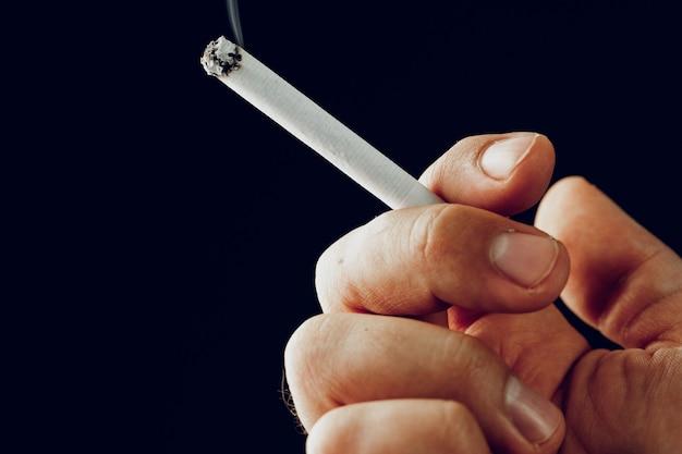 Männliche hand mit einer brennenden zigarette gegen schwarze nahaufnahme