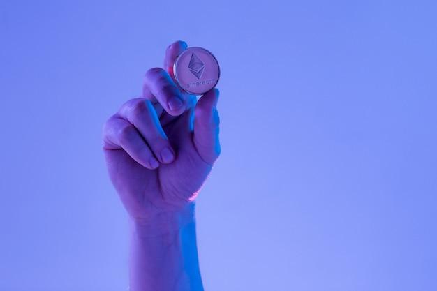 Männliche hand mit goldenem ethereum auf blauem hintergrund