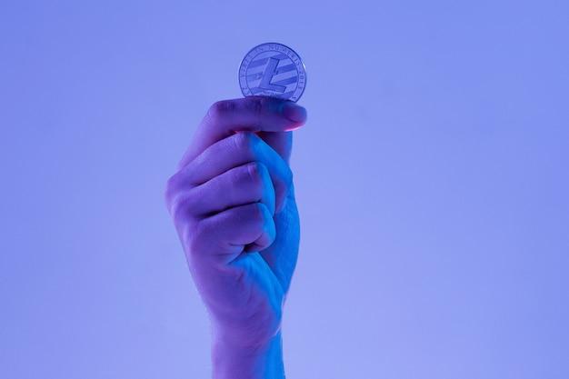 Männliche hand mit goldenem litecoin auf blauem hintergrund