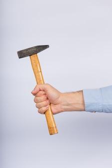 Männliche hand mit hammer auf weißem hintergrund. klauenhammer seitenansicht.