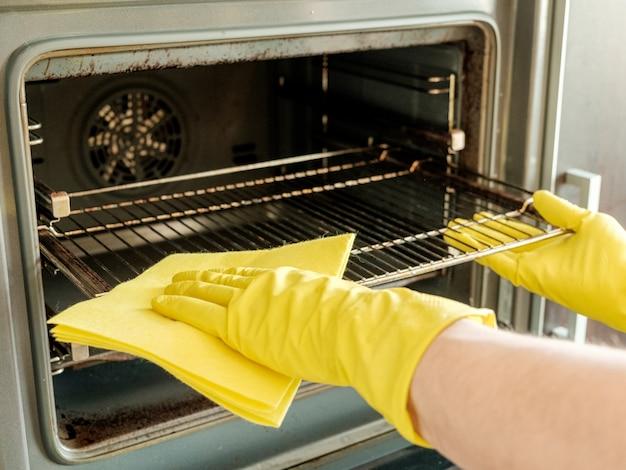 Männliche hand mit handschuhen, die ofen reinigen