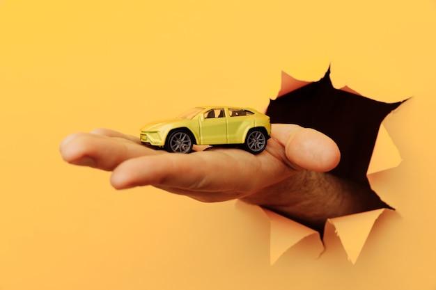 Männliche hand mit hausauto durch einen riss in der gelben papierwand. verkaufs- und mietkonzept.