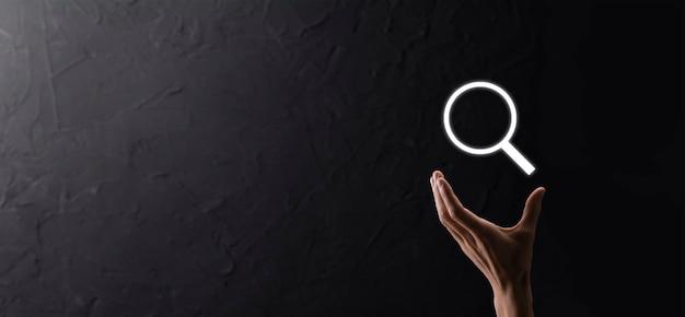 Männliche hand mit lupe, suchsymbol auf blauem hintergrund. konzept suchmaschinenoptimierung, kundensupport.browsing internet data information.networking konzept.