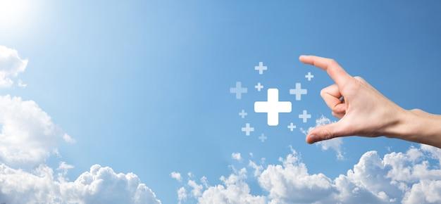 Männliche hand mit plus-symbol auf blauem hintergrund. pluszeichen virtuell bedeutet, positive dinge wie vorteile, persönliche entwicklung, soziales netzwerk gewinn, krankenversicherung, wachstumskonzepte anzubieten