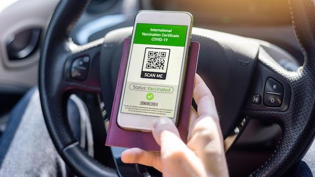 Männliche hand mit reisepass und smartphone mit internationalem impfzertifikat covid-19 qr-code in einem auto