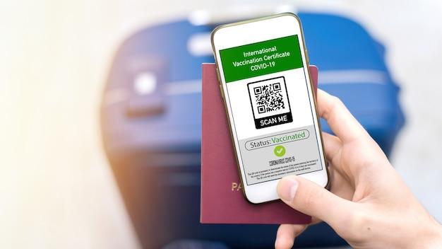 Männliche hand mit reisepass und smartphone mit internationalem impfzertifikat covid-19 qr-code, koffer