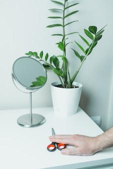 Männliche hand mit schere gegenüber dem spiegel. zu hause bleiben.