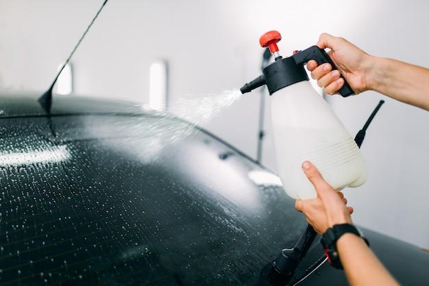 Männliche hand mit spray, installationsprozess der autofenstertönung, installationsverfahren, tönungsfolie